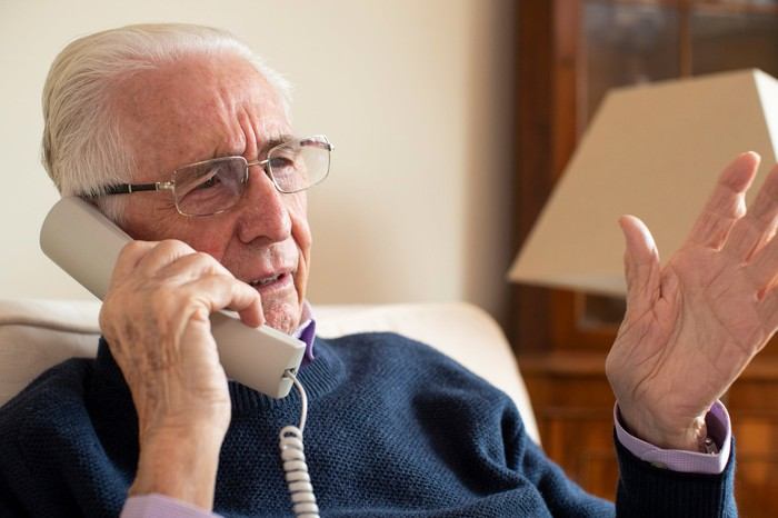 Older man with concerned expression talking on phone