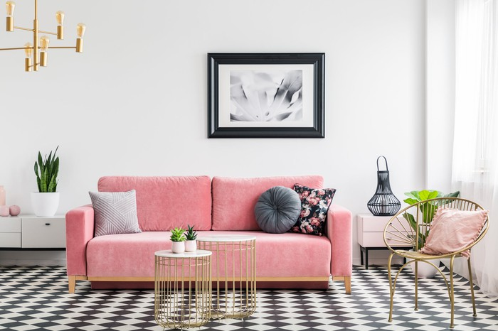 A pink couch in a well-lit living room.
