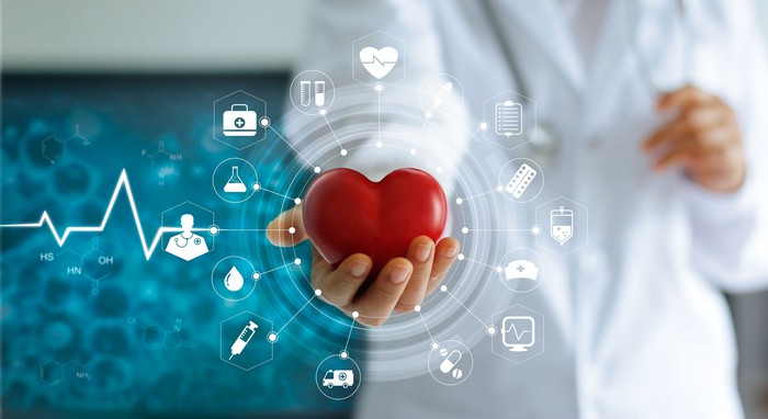 A person in a white lab coat holding out a stylized red heart with some digital icons surrounding it