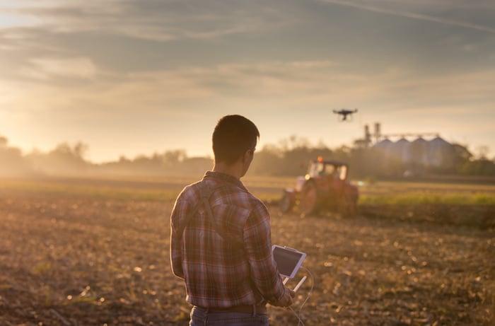 A man piloting an aerial drone over farmland fields.