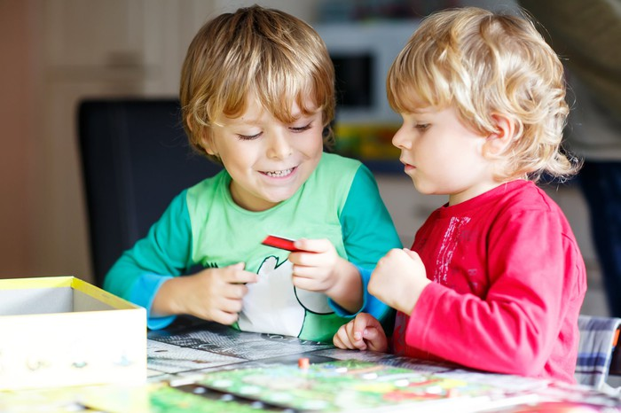 Two children sitting at a table playing a board game.