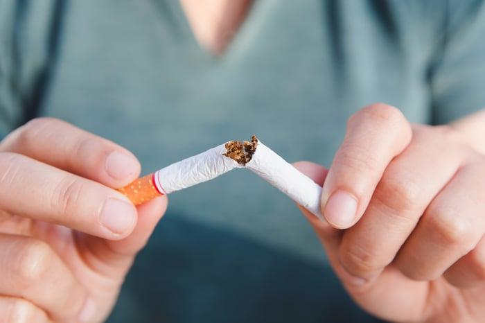 A man snaps a cigarette in half.