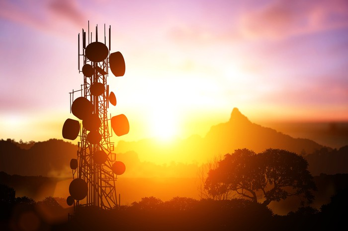 Silhouette of a heavily equipped cell tower against a colorful sunset.