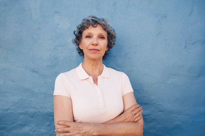 Older woman with crossed arms and serious expression against a blue background