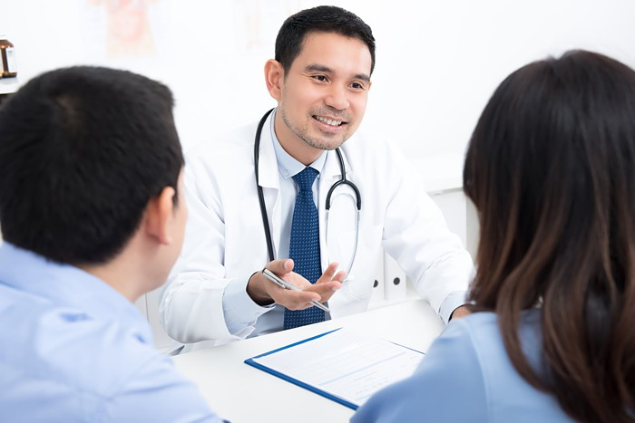 Doctor sitting across from couple