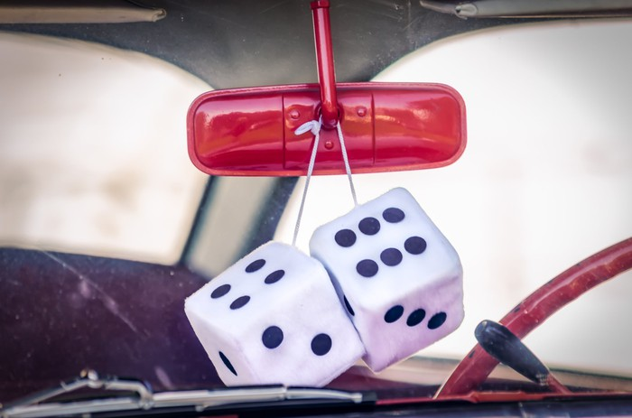 Fuzzy dice hang from a red rearview car mirror