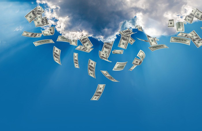 Money falling out of dark clouds against a blue sky.