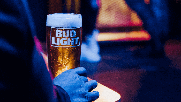 Hand holding glass of Bud Light beer