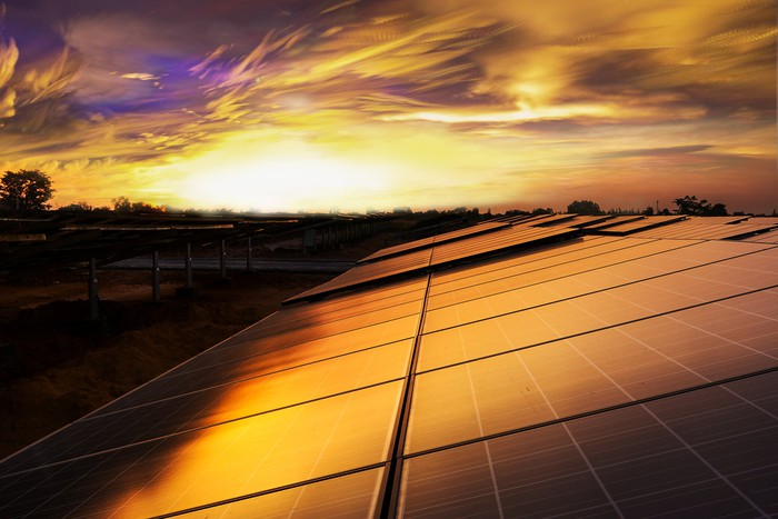 Solar panels on a rooftop with the sun setting in the background.