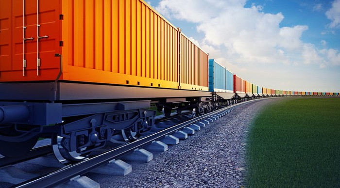 Colorful box cars against the blue sky as a freight train rounds a bend.