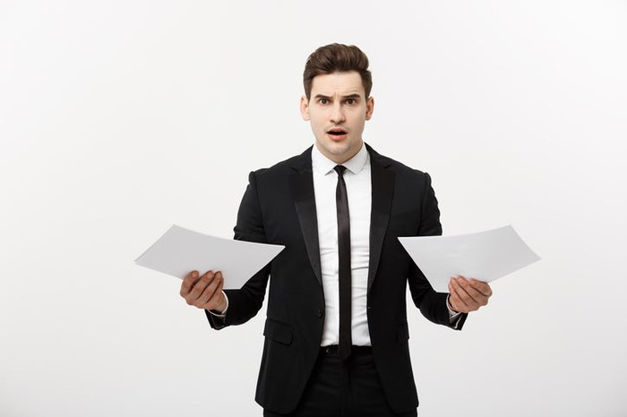 A businessman holding a piece of paper in each hand with a nervous look on his face.