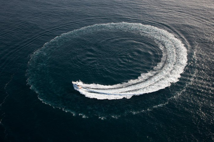 A boat at sea turning around in a tight circle.