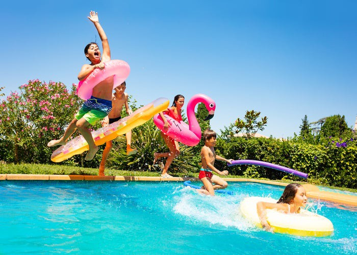 Three young boys and two young girls -- each with an inner tube or raft -- in various states of jumping into an in-ground swimming pool with foliage and blue sky in background.