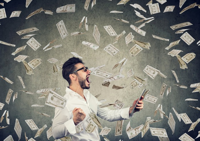 Man with tablet among swirling money