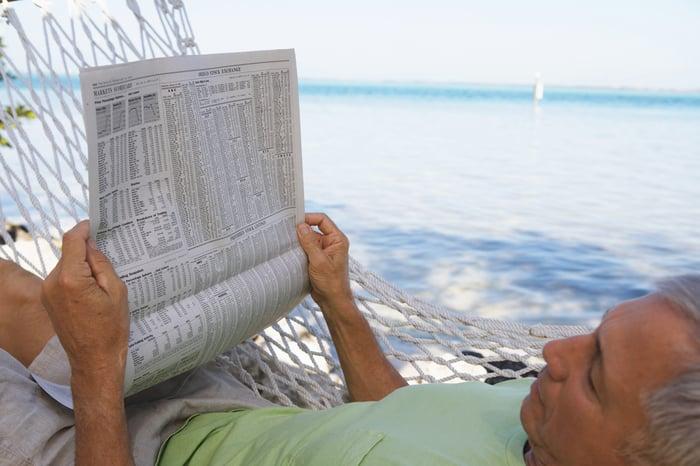 A man resting in a hammock near the ocean reading a newspaper.