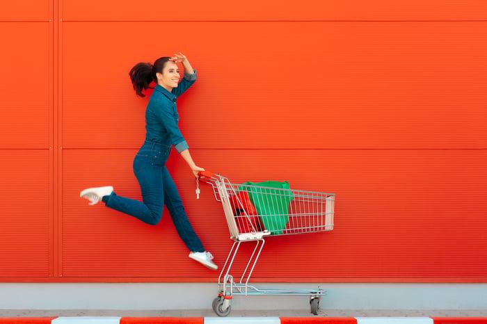 A woman skipping as she pushes a shopping cart.