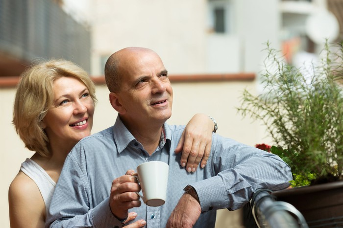 Middle-aged woman putting arm around middle-aged man holding mug