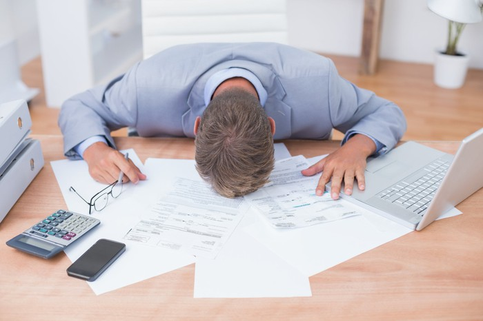 Man putting his head down on a table with spread-out papers, laptop, calculator, glasses, and phone