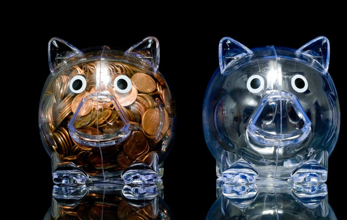 Two transparent piggy banks, one full of pennies and the other empty
