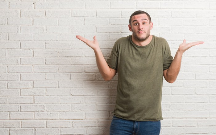 Man standing against a brick wall, shrugging