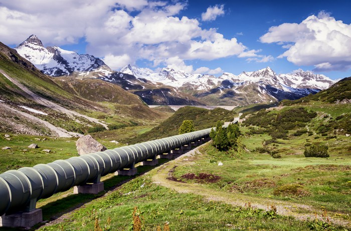 A pipeline with a snow covered mountain in the background.