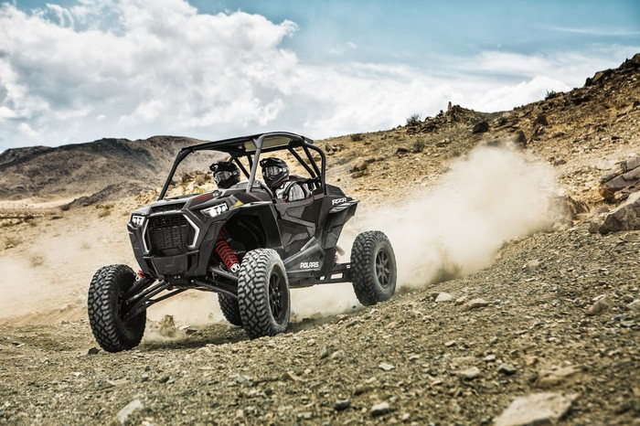 Two-seat Polaris RZR spraying dust behind it on a rocky mountain landscape.