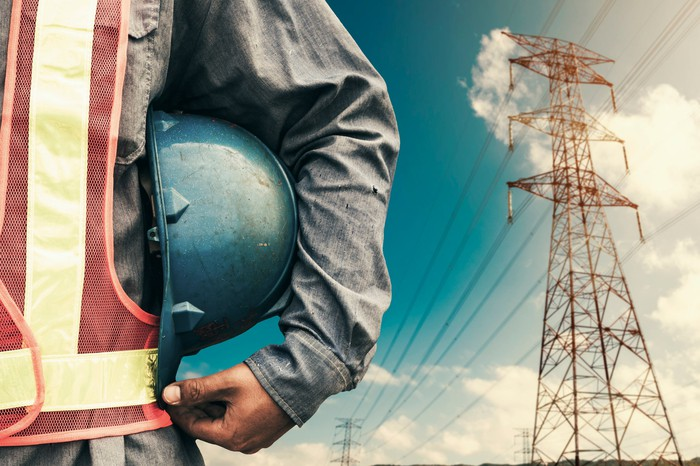 A close-up of a hard hat under a man's arm, with power lines in the background