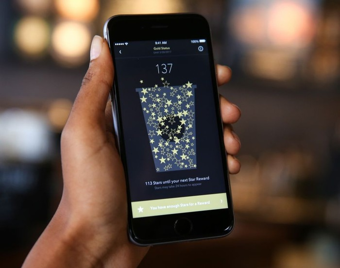 A person holds up a phone running the Starbucks app.