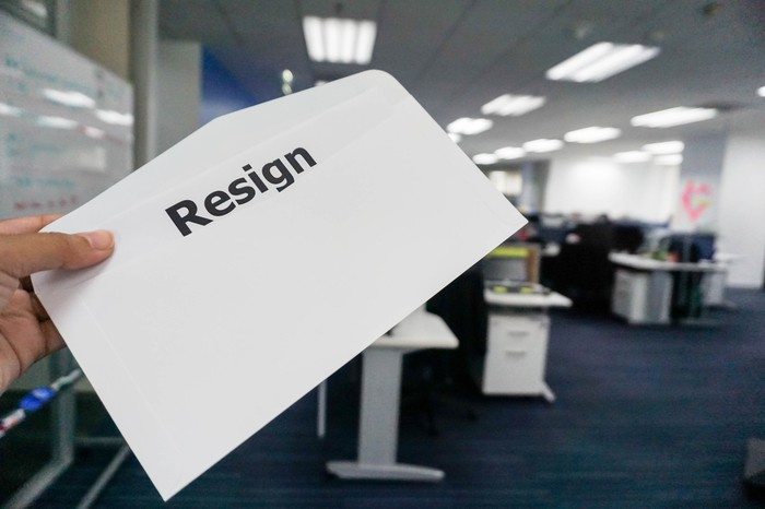 Person holding a while envelope with the word resign printed in black