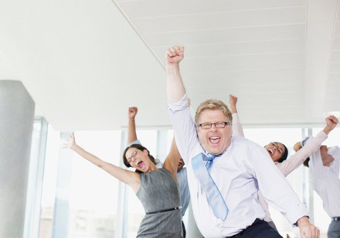 Business people cheering with their hands in the air