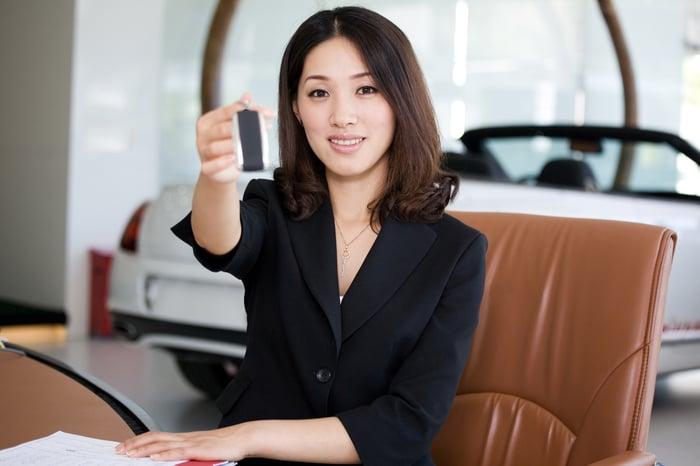 A car dealer hands a key to a customer.