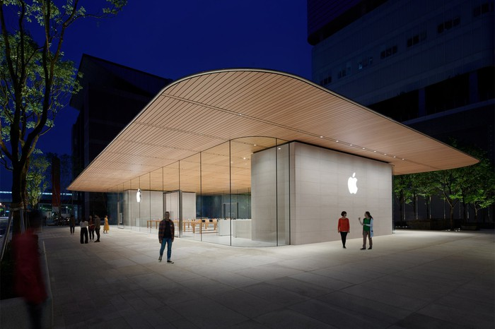 The new Apple store in Taipei with a wooden roof overextending the glass exterior and the white Apple logo displayed on the side of the building.
