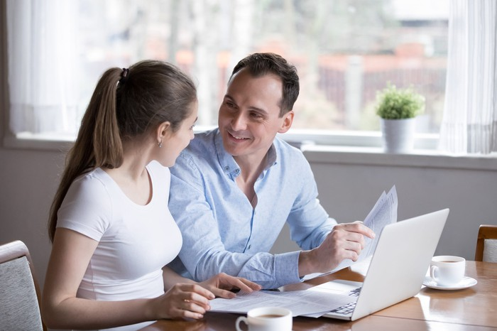 Smiling couple with documents at a laptop