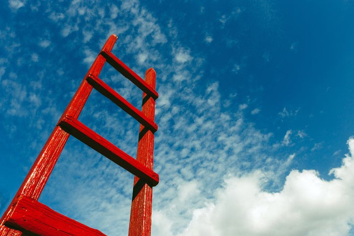 A red ladder leading to a blue sky.