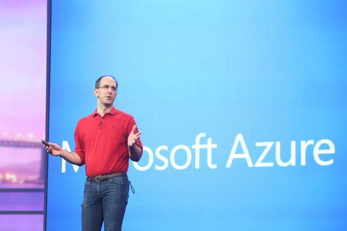 A Microsoft executive in front of a large screen with the words Microsoft Azure.