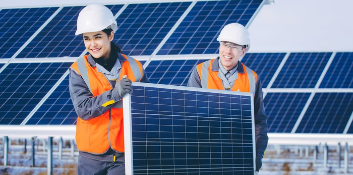 Two people carrying a solar panel with a solar farm in the background