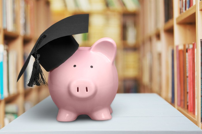 Piggy bank with a college graduation cap on