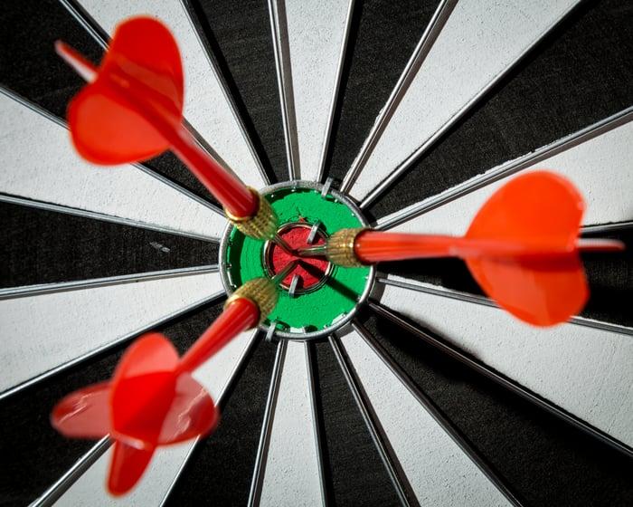 Three darts in the bullseye of a target board