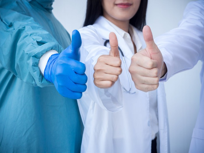 Three healthcare professionals standing together and holding their thumbs up.