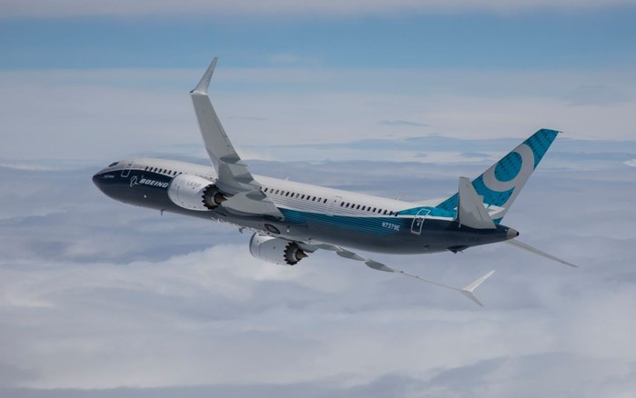 A Boeing 737 MAX 9 flying over clouds.