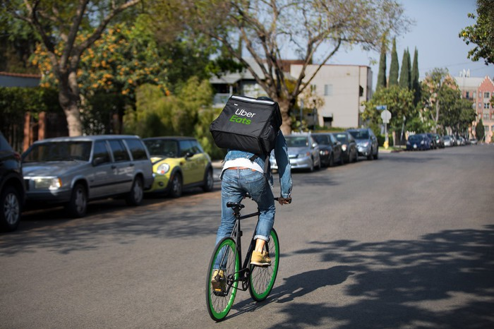 Man on a bike with an Uber Eats insulated carrier on his back