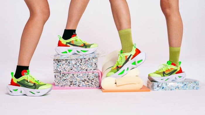 Two pairs of feet standing on a towel and exercise blocks wearing the new Nike ZoomX in bright red and green colors.