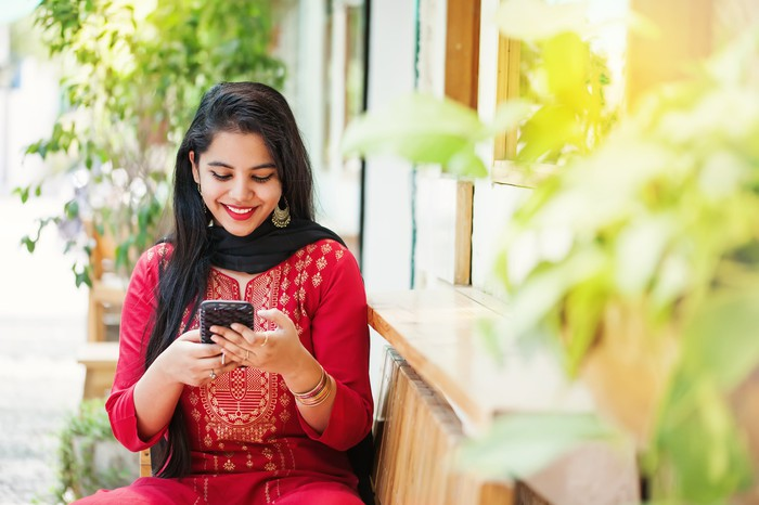 Young Indian woman in a bright red outfit looking at her phone.