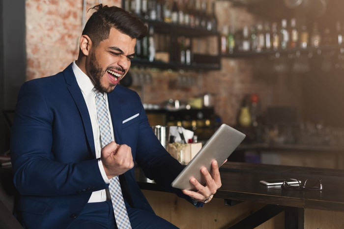 A man pumps his fist in joy while looking at something on his tablet in a bar.