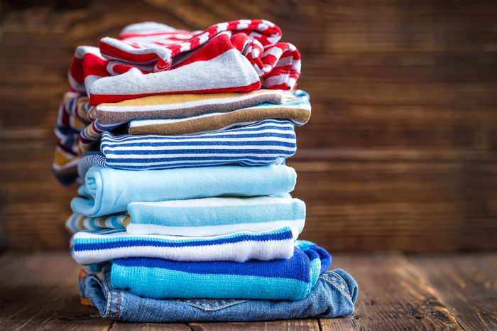 Stack of colorful folded children's clothing on a wood floor.
