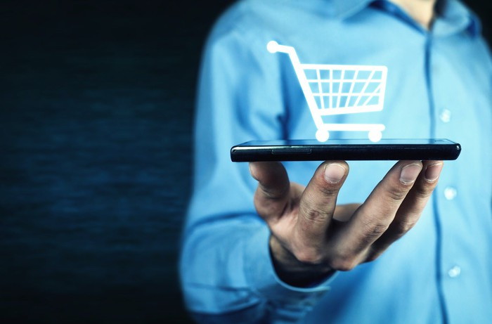 Man holding smartphone flat on his fingertips with digital shopping cart glowing on top.