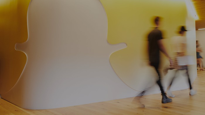 Two Snapchat employees walking past a mural with the ghost mascot.
