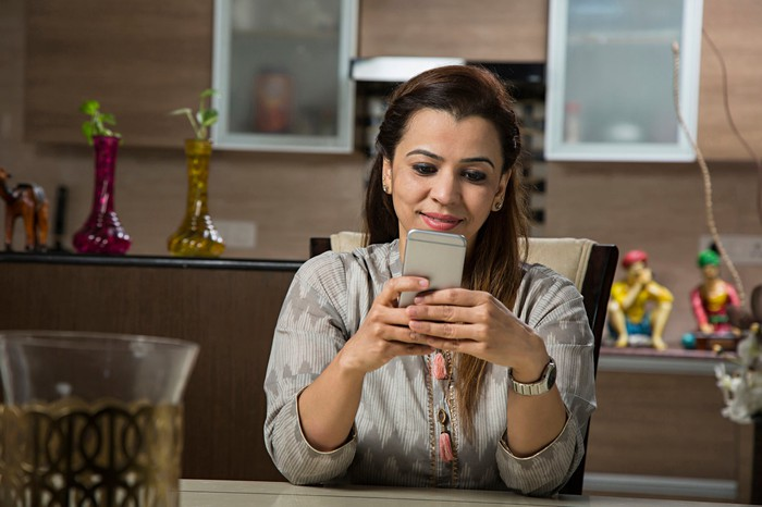 A woman sits at a table and looks at her smartphone