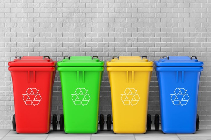 Four recycling containers, in red, green, yellow, and blue, in a row against a gray brick wall.