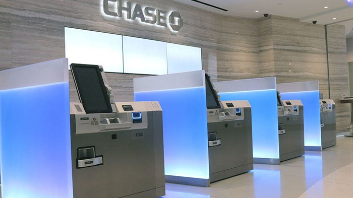 Inside of a Chase banking branch with four ATMs lined up against a wall.